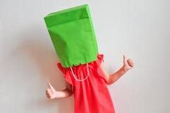 有一个包裹的一个滑稽的女孩在她的头显示她拇指并且喜欢在轻的背景的购物和销售 好心情的孩子 库存图片