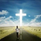 有一个十字架的男性吉他弹奏者在路 免版税库存图片