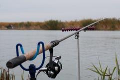 有一个卷轴的钓鱼竿在河附近 钓鱼在鲤鱼,鲂 免版税库存照片