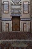 有一个历史的华丽木门的老装饰的石墙 免版税库存照片