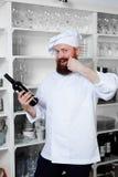 有一个厚实的胡子的逗人喜爱的厨师选择一个瓶客人的昂贵的酒 免版税库存照片