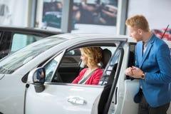有一个友好的经销商汽车测试新的模型的顾客 库存图片