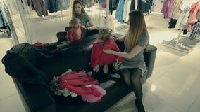 有一个可爱宝贝女孩的年轻美丽的母亲在尝试在镜子前面的衣裳的商店 股票录像