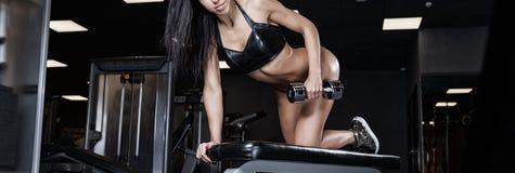 有一个哑铃的性感的运动员在健身房 免版税库存图片