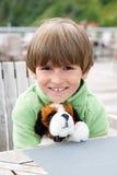 有一个喜爱的软的玩具的微笑的男孩 库存照片
