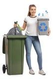 有一个回收站和垃圾袋的女孩 库存图片