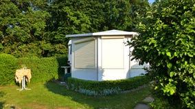 有一个固定的游廊的有蓬卡车由遮篷织品、玻璃可调整窗口和窗帘做成在德国露营地 图库摄影