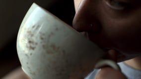 有一个圆环的女孩在他的鼻子喝从一个杯子特写镜头的咖啡在咖啡馆 股票录像