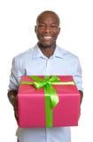 有一个圣诞节礼物的非洲人在他的手上 免版税库存照片