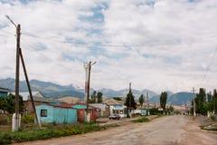 有一个地板大厦和山背景的小中亚镇 库存照片