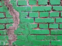有一个垂直的裂缝的一个绿色砖墙关闭了与灰色水泥 免版税库存照片