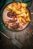 有一个外壳和被烘烤的土豆的烤猪肉内圆角在有叉子的,顶视图板材 免版税库存照片