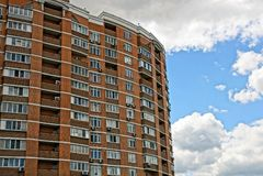 有一个多层的棕色大厦的城市街道与窗口和阳台 库存照片
