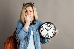 有一个大时钟的女学生在手上 在一个灰色背景 库存图片