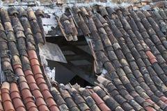 有一个大漏洞的老铺磁砖的屋顶 免版税库存图片