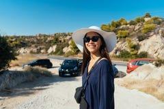 有一个大白色帽子的一名年轻苗条妇女在夏天 图库摄影