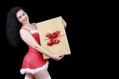 有一个大礼物盒的圣诞节肉欲的深色的女孩,隔绝在黑色 免版税库存照片