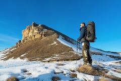 有一个大背包和棍子的背包徒步旅行者登高对在日落的岩石以在的史诗岩石为背景 免版税库存图片