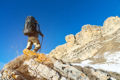 有一个大背包和棍子的背包徒步旅行者登高对岩石以史诗岩石为背景在冬天 免版税库存图片