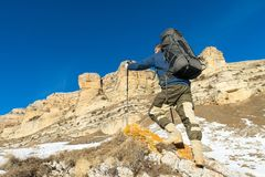 有一个大背包和棍子的背包徒步旅行者登高对岩石以史诗岩石为背景在冬天 库存照片