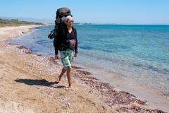 有一个大背包的游人走通过地中海清楚的水的  库存图片