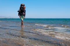 有一个大背包的游人走通过地中海清楚的水的  库存照片