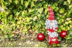 有一个大胡子的圣诞老人在两个圣诞节球旁边 免版税库存照片