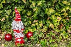 有一个大胡子的圣诞老人在两个红色圣诞节球旁边 库存照片