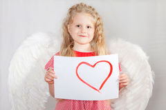 有一个天使的翼的白肤金发的女孩在情人节看板卡的 库存照片