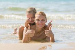 有一个女儿的妈咪他的说谎在海滩和展示的后面 女孩和妇女展示赞许 免版税库存图片