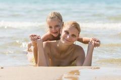 有一个女儿的妈咪他的说谎在海滩和微笑的后面 免版税库存照片
