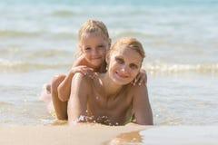 有一个女儿的少妇他的说谎在海滩和微笑的后面 免版税库存照片