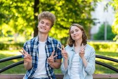 有一个女孩的一个人在夏天在一个公园本质上 愉快微笑的情感愉快 手姿态显示你好 的treadled 库存照片