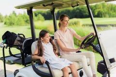 有一个女孩的妇女去一辆白色的高尔夫车的打高尔夫球 免版税库存图片