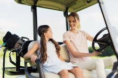 有一个女孩的妇女去一辆白色的高尔夫车的打高尔夫球 免版税图库摄影