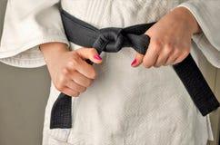 有一个女孩的指甲油的手有黑腰带级选手的在武术, 免版税库存图片