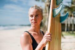 有一个委员会的美丽的运动员女孩冲浪者日出的 健康生活方式和活跃休息 免版税库存图片