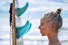有一个委员会的美女冲浪者日出的 海上的暑假,健康生活方式 免版税库存图片