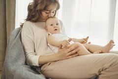 有一个婴孩的一个母亲她的胳膊的坐一把椅子在前面 库存图片