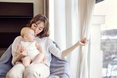 有一个婴孩的一个母亲她的胳膊的坐一把椅子在前面 免版税库存照片