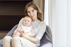 有一个婴孩的一个母亲她的胳膊的坐一把椅子在前面 图库摄影
