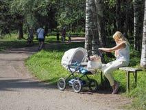 有一个孩子的一名妇女休息在公园的婴儿推车的 俄国 圣彼德堡 夏天2017年 库存图片