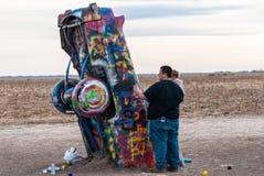 有一个孩子的人乘构成卡迪拉克大农场纪念碑的部分汽车在阿马里洛,TX 库存照片