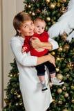 有一个孩子的典雅的祖母她的在圣诞树的背景的胳膊的 库存照片