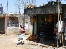 有一个孩子的可怜的亚裔妇女在一家小商店附近,斯里兰卡 免版税库存照片