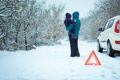 有一个孩子的妇女冬天路的 库存图片