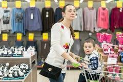 有一个孩子的妈妈一辆台车的在购物中心 有一个小儿子的妈妈在购物中心 库存图片