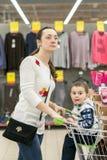 有一个孩子的妈妈一辆台车的在购物中心 有一个小儿子的妈妈在购物中心 驾驶一个年轻儿子的妈妈到商店 免版税库存照片