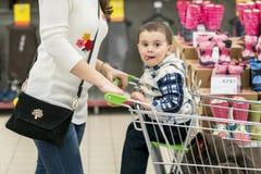 有一个孩子的妈妈一辆台车的在购物中心 有一个小儿子的妈妈在购物中心 驾驶一个年轻儿子的妈妈 图库摄影