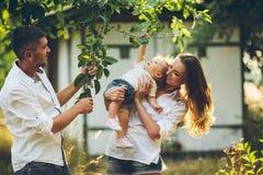 有一个孩子的家庭在夏天从事园艺 免版税图库摄影